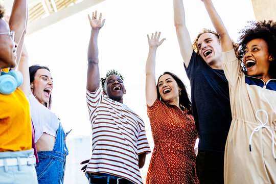 Group of young friends raising their hands in unity - Happy multiracial people having fun together and celebrating victory outdoors - Low angle view - Unity, integration and community concept - Focus