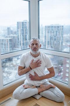 A mature yogi doing pranayama and looking meditative