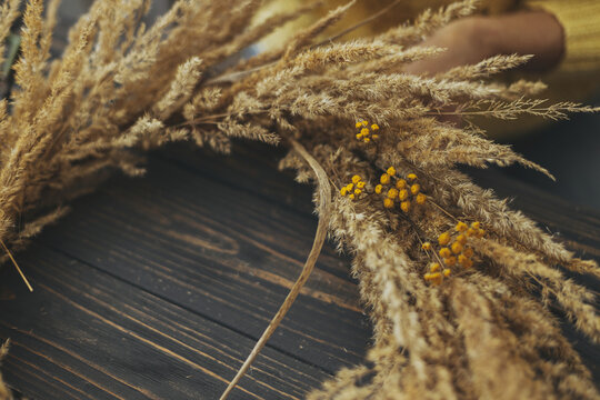 Stylish autumn boho wreath with dry grass and wildflowers on rustic wooden background. Making rustic autumn wreath with pampas grass and yellow tansy flowers, holiday workshop