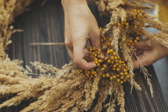 Hands making stylish rustic autumn wreath with dry grass and tansy wildflowers on dark wooden background. Holiday workshop. Florist in yellow sweater making boho wreath on wooden table