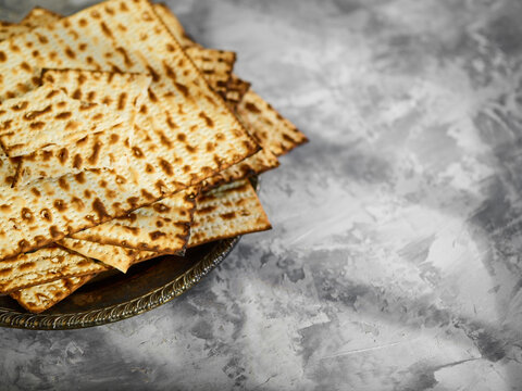 Matzah is a traditional kosher Jewish Passover bread. The great holiday is Jewish Passover. Beautiful light background. There is no one in the photo. There is an empty space for your insert.