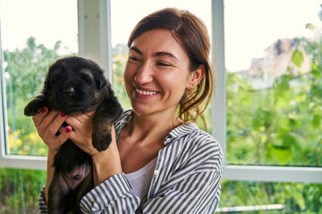 Obraz Happy woman spending time with cute black puppy - fototapety do salonu