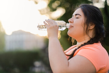 Fototapeta Dehydrated woman. Water thirst. Nutrition wellness. Body healthcare. Side view portrait of obese overweight drinking lady in defocused copy space sunset background. obraz