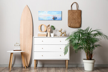 Fototapeta Interior of modern stylish room with chest of drawers and surfboard obraz