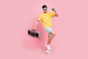 Full size photo of cheerful young happy man hold hands boombox drink dance isolated on pink color background