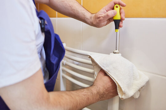Plumber installs radiators in bathroom