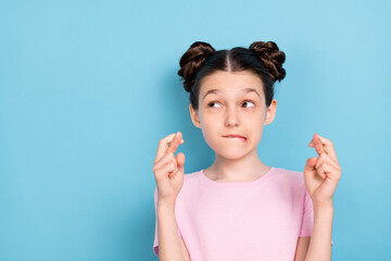 Photo of minded curious young small girl fingers crossed look empty space isolated on pastel blue color background Wall mural