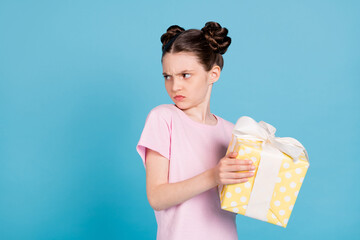 Obraz Photo of furious unhappy school girl wear pink t-shirt holding yellow present box looking empty space isolated blue color background - fototapety do salonu