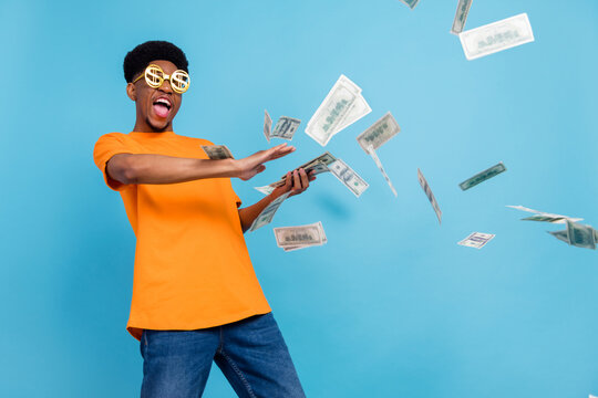 Photo of young happy dark skin crazy man fly money rain wear funny glasses isolated on blue color background