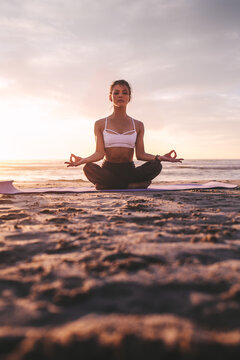 Woman meditating in lotus pose during sunset