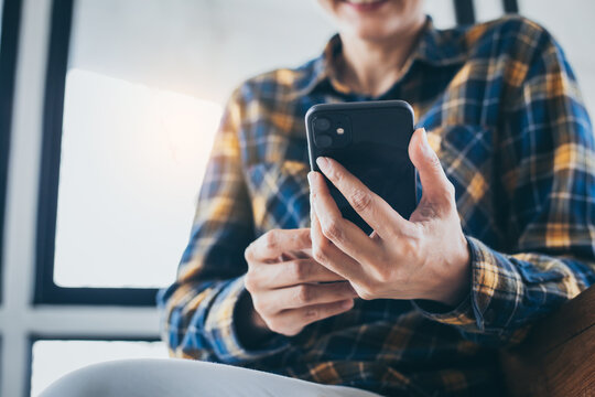 using cell phone hand holding mobile texting message contact us.chatting,search internet information in office.technology device communication connecting