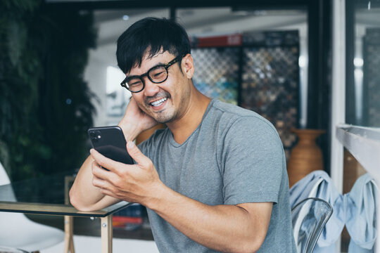 asian man work using cell phone hand holding mobile texting message contact us.chatting,search internet information in office.technology device communication connecting