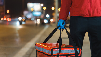 Obraz Close-up shot of a food deliveryman in red uniform carrying a food delivery box to deliver for customer for order during COVID-19 outbreak lockdown in the city at night time - fototapety do salonu