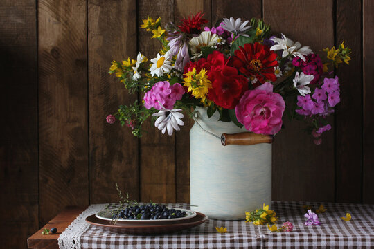 still life with a bouquet of garden flowers and blueberries.