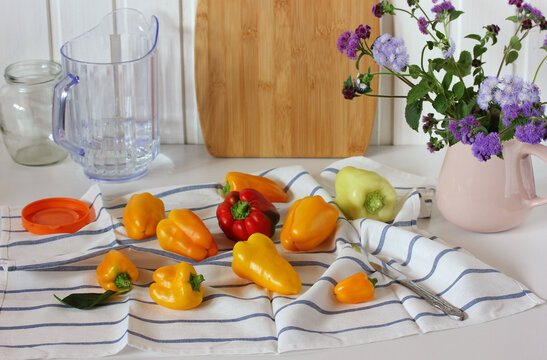 kitchen table with bell peppers on a towel and a bouquet in a jug. summer still life.