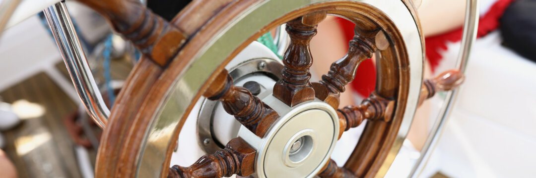 Wooden vintage steering wheel on a yacht close-up