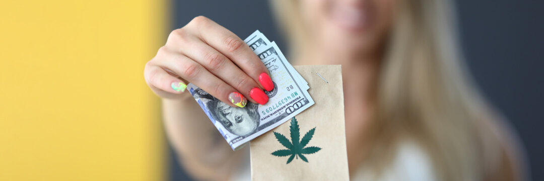 Woman holding package with marijuana and money