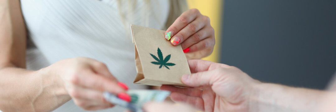 The woman gives money and receives bag marijuana