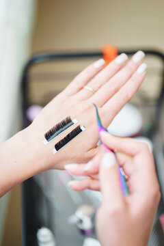 Aesthetic medicine, eyelash extension process: girl's hand with tools