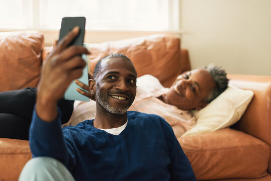 Husband taking selfie together with wife while relaxing on the couch
