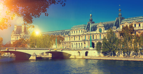 Obraz View of Pont du Carrousel across Seine river leading to arched entrance to Louvre palace courtyard, Paris, France.. - fototapety do salonu