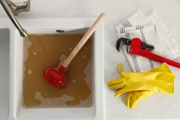 Fototapeta Kitchen counter with clogged sink, plunger and plumber's accessories, flat lay obraz