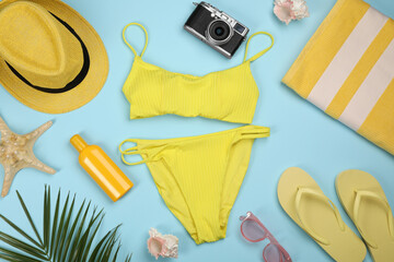 Fototapeta Flat lay composition with swimsuit and beach accessories on light blue background obraz