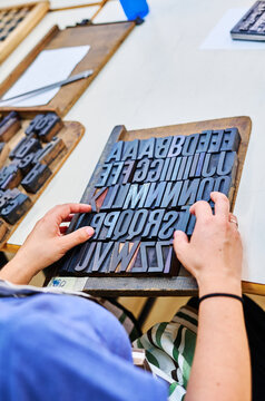 Crop man working with font of metal letters in typography