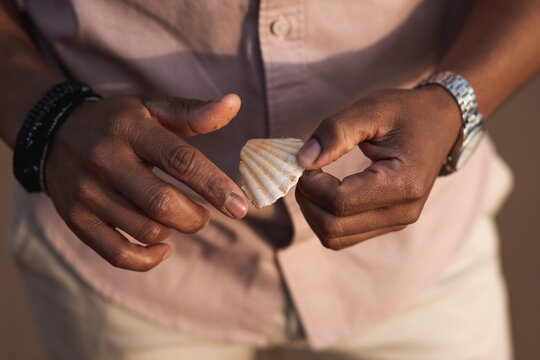Ethnic man with accessories holding seashell