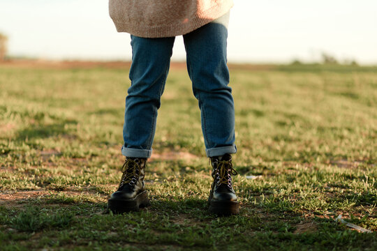 Woman in jeans and boots standing in field