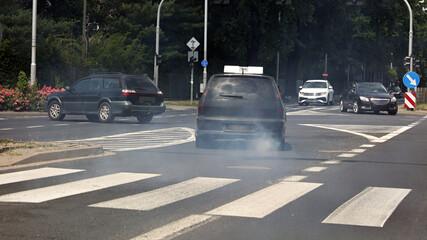 Fototapeta Stary samochód spalinowy z silnikiem diesla zanieczyszczający miasto. obraz