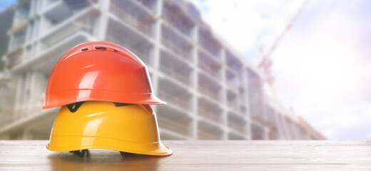 Fototapeta Hard hats on wooden surface at construction site with unfinished building, banner design. Space for text obraz