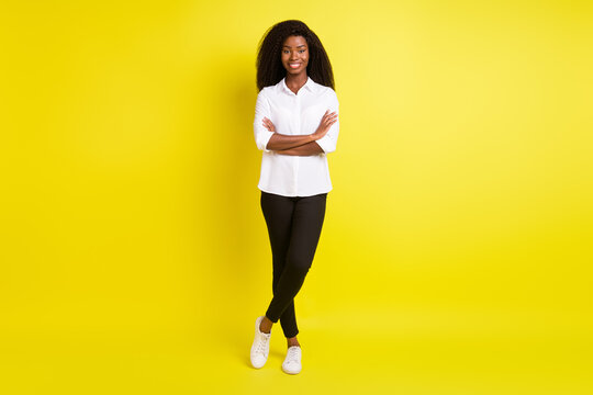Full length body size photo smiling girl with folded hands wearing white shirt smiling happy isolated bright yellow color background