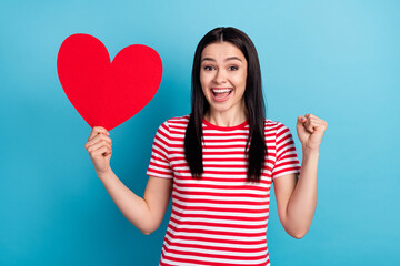 Photo of young excited girl happy positive smile hold big heart rejoice win lucky romantic isolated over blue color background Wall mural