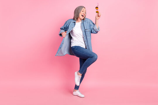 Full length photo of cool senior lady dance wear blue shirt jeans sneakers isolated on pink color background