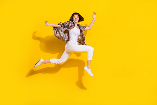 Full length body size view of attractive sporty cheerful girl jumping running motion isolated bright yellow color background