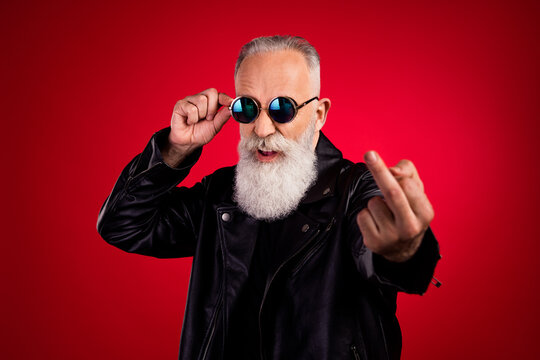 Portrait of attractive fashionable elderly grey-haired man showing middle finger touching specs isolated over bright red color background