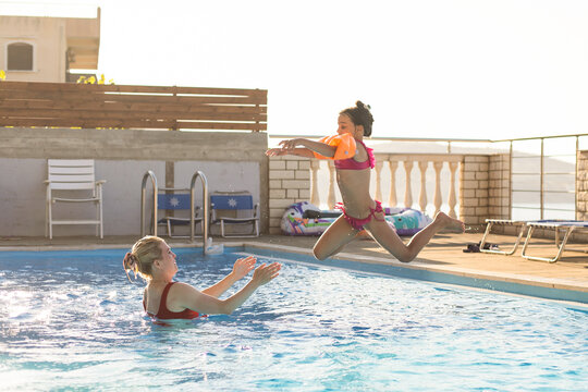 beautiful woman catches little girl jumping in pool against sea