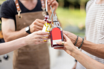 Fototapeta People clinking bottles with a strong alcohol drinks on a picnic outdoors, close-up. Holding bottles of liqueur or tinctures obraz