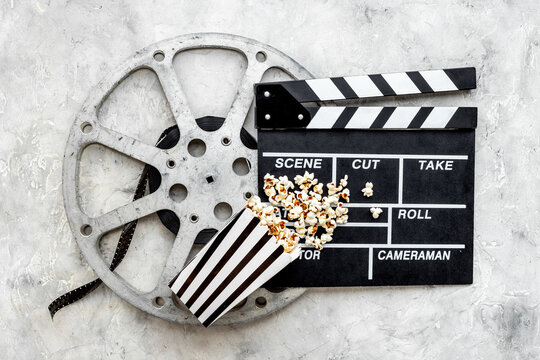 Cinema concept. Popcorn with film reel strip and clapper board