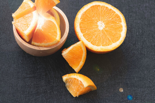 Cutted of Orange put beside blurred wood cup with fruit, on background,