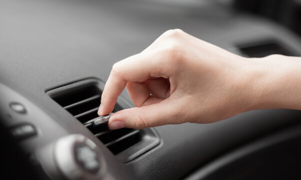 The hand adjusts the air conditioner in the car. Close up