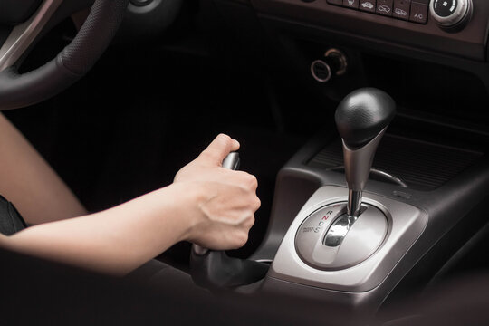 Driver pulling the hand brake in car. Close up
