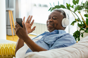 Senior African man sitting at home with headphones on and having a video call with loved ones. He is waving and he is happy to see his best friend.