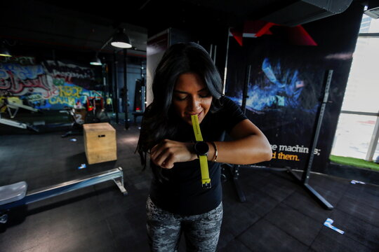 Shaikha al Shaiba, a Bahraini amputee and cancer survivor, uses her mouth to wear a watch at a local gym in Manama