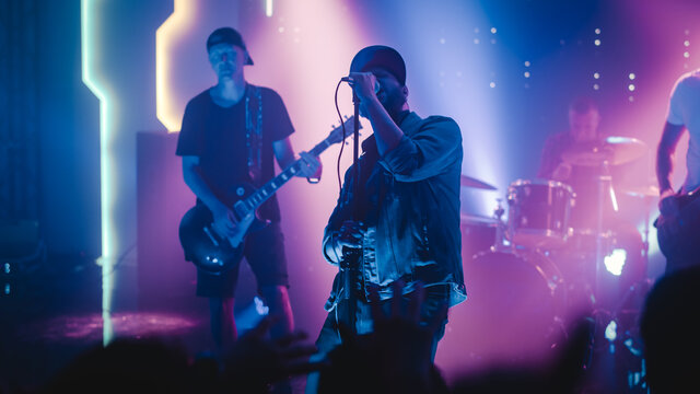 Rock Band with Guitarists and Drummer Performing at a Concert in a Night Club. Lead Singer Singing into Microphone. Live Music Party in Front of Bright Colorful Strobing Lights on Stage.