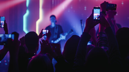 Fototapeta Rock Band with Guitarists and Drummer Performing at a Concert in a Night Club. Front Row Crowd is Record Video on Their Mobile Phones. Party in Front of Bright Colorful Strobing Lights on Stage.  obraz