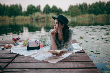 Fototapeta a girl on a picnic by the lake drinks rose wine and reads a book obraz