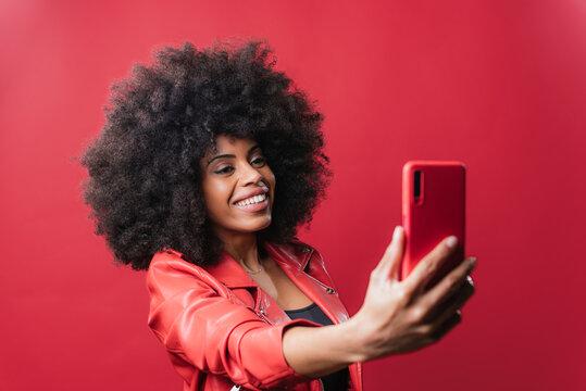 Black woman taking selfie on smartphone in studio