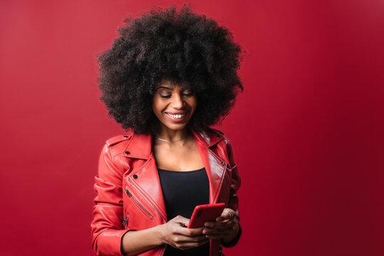Black woman browsing smartphone in studio